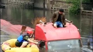 Firefighter uses dinghy to rescue lorry driver trapped on flooded road - Video