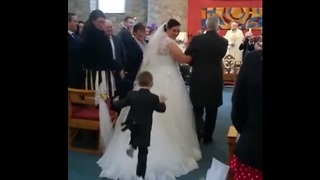 Kid dives onto back of bride's wedding dress during ceremony - Video