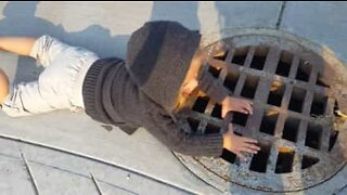 2-year-old girl talks into a sewer