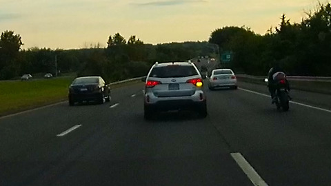 Impatient tailgating car cuts over 2 lanes almost hitting motorcycle.