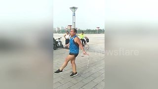Man performs skipping rope moves in city square