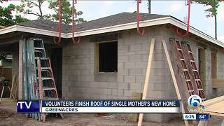 Volunteers finish roof of single mother's new home - Video