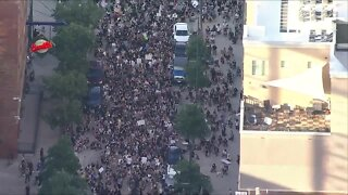 Protesters march outside of Coors Field for George Floyd
