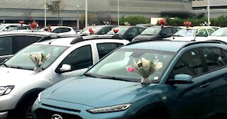 Florist Places Bouquets On Every Car In A Hospital Parking