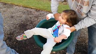 Toddler Girl Can't Stand Up After Spinning In A Seat On A Playground - Video