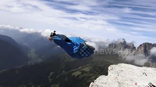 Incredible stunt shows wing-suit pilot dive past Dolomites highliner - Video