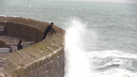 Huge waves crash over harbour wall in Cornwall drenching locals braving the rough seas