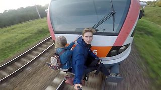 The couple that train surf together, stay together: Extreme couple have unconventional date while clinging on to speeding train - Video