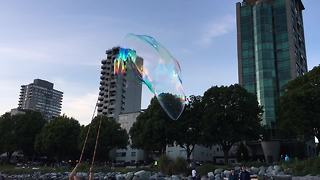 Bubble artist dazzles crowd with massive floating bubbles - Video