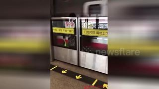 Woman trapped behind subway safety doors as train speeds by - Video