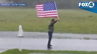 Guy with flag braves Hurricane Irma - Video