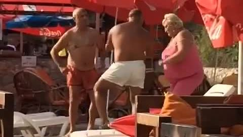 Elderly people at the beach dance to rap music