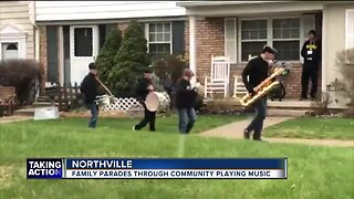 Family parades through community playing music