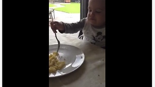 Toddler Takes Real Delight Into Munching Macaroni With Two Forks - Video