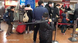Shocking moment young child carries realistic rifle over his shoulder on to packed Shanghai subway - Video