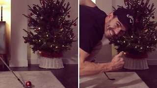 Man decorates christmas tree with golf club - Video