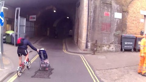 'Stupid' dad on bike pushes daughter in pram down middle of London street with one hand