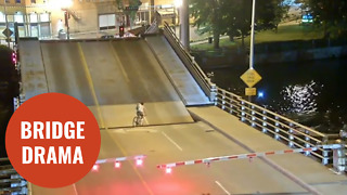Cyclist ignores bridge warning barriers and falls into gap of drawbridge - Video