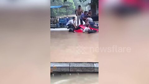 Residents in Chinese town rescue tourists trapped in SUV before it sunk into flooded river
