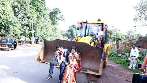 Indian groom takes his bride home inside bucket of JCB digger