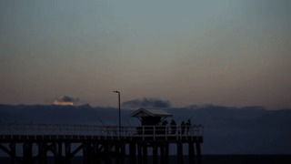 Supermoon Rises Over Fishermen on Cloudy Evening - Video