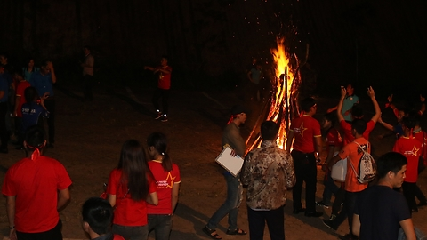 Funny dancing by fire at campfire in the forest