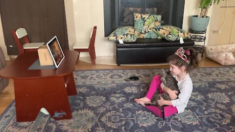 Little girl adorably struggles with remote learning due to affectionate kitten