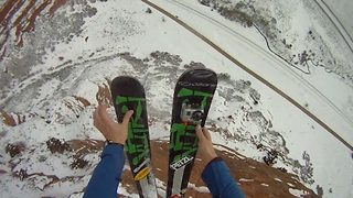 Daredevil skis into parachute free fall from cliff edge - Video
