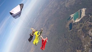 Canopy pilots and wingsuiters jump from 13,00o foot in daredevil stunt  - Video