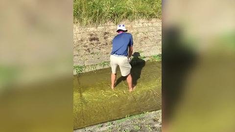 A Man Tries To Hit A Golf Ball In Shallow Water But Fails