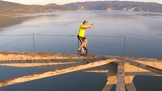 Daredevil Unicyclist Rides Along Narrow Girders of Steel-Frame Bridge - Video