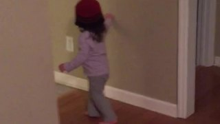 Tot Girl Puts A Beanie Over Her Head And Navigates Around A House - Video