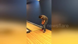 Man's fingers get stuck in bowling ball as he goes bowling for the first time - Video
