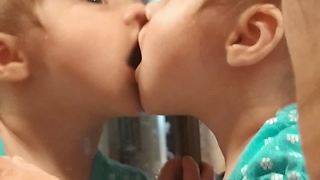 Sweet baby shares kisses with her reflection - Video