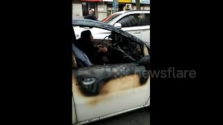Woman drives burnt-down car on road - Video