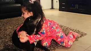 Little girl preciously paints her doggy's nails