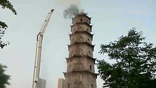 Firemen use crane to water tree growing on top of ancient pagoda - Video