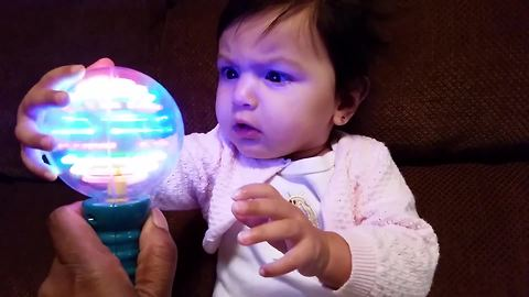 A Baby Girl Stares At A Spinning Ball Of Light And Furrows Her Brow