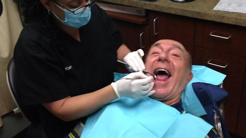 Boy films his father at the dentist.