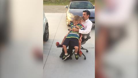 Kids Having Fun With Their Dad Riding An Office Chair