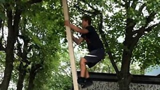 Youth climbs ladder without support, does a backflip from a tree
