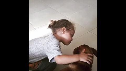 Little boy gives his dog sweet kiss