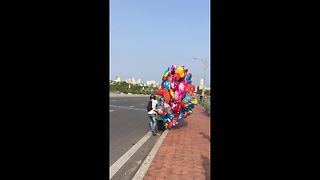 Balloon salesman struggles in high winds on Vietnam road - Video