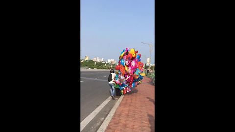Balloon salesman struggles in high winds on Vietnam road