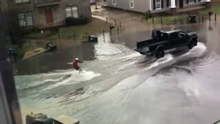 Guy goes water skiing during floods