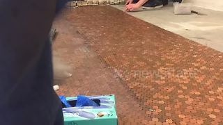 Shop owner decorates floor with thousands of pennies - Video