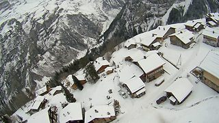 Gliding in a winter wonderland: Paragliding thrillseeker traverses over tranquil 'post-card' moutain-top town - Video