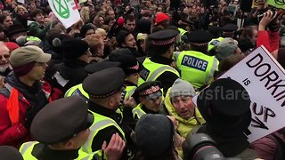Scuffles break out as police force their way into London climate protest