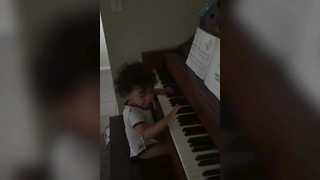 An Adorable Little Boy Plays The Piano