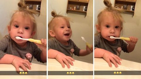Little Girl Pretends She Is Using An Electric Toothbrush To Copy Dad